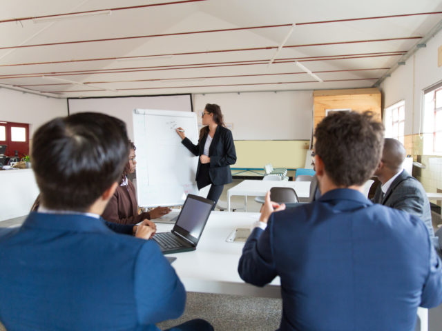 Confident female businesswoman drawing on whiteboard. Group of workers sitting at table and listening speaker. Business meeting concept